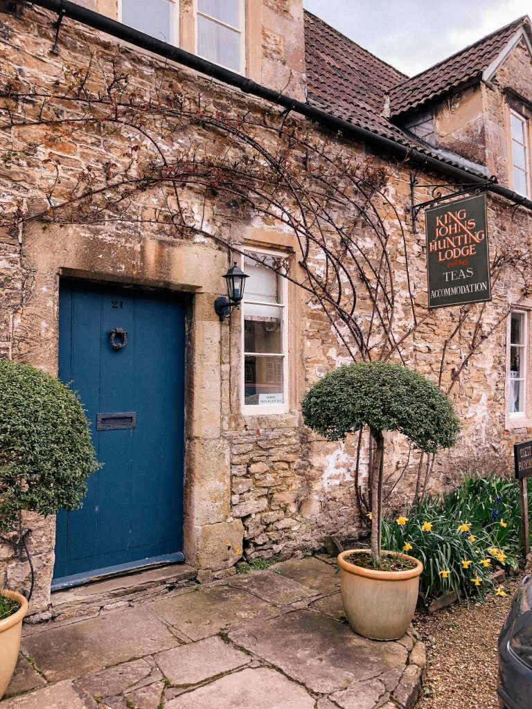 Lacock, Wiltshire, Cotswolds, UK, National Trust, England, English Countryside, blue doors, orange wheelbarrow, daffodils, spring, easter