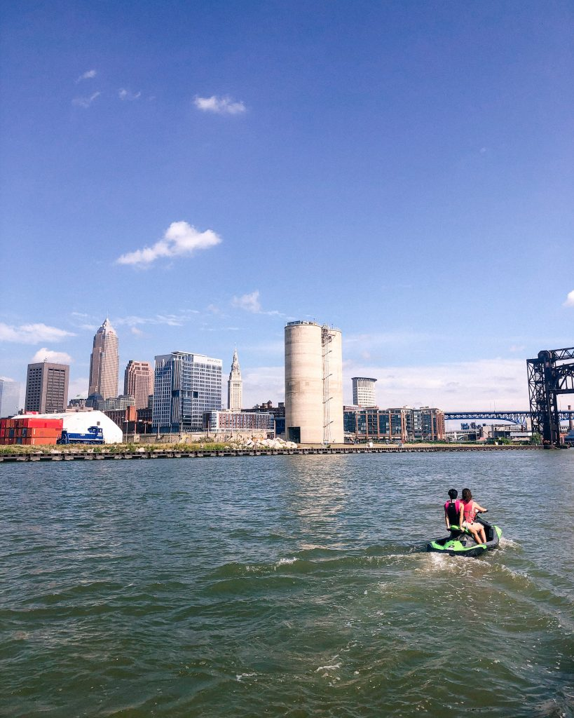 Jet Skiiers on the Cuyahoga River off of Lake Erie with Cleveland skyline and blue skies.