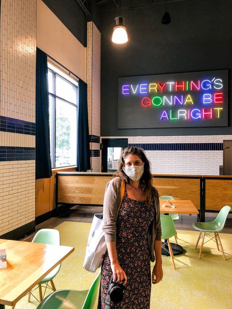 "Woman in face mask in front of rainbow light up sign reading ""Everything's gonna be alright"""
