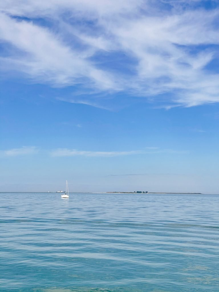 White sail boat in the distance on calm blue waters with a pure blue sky and fluffy white clouds in the sky