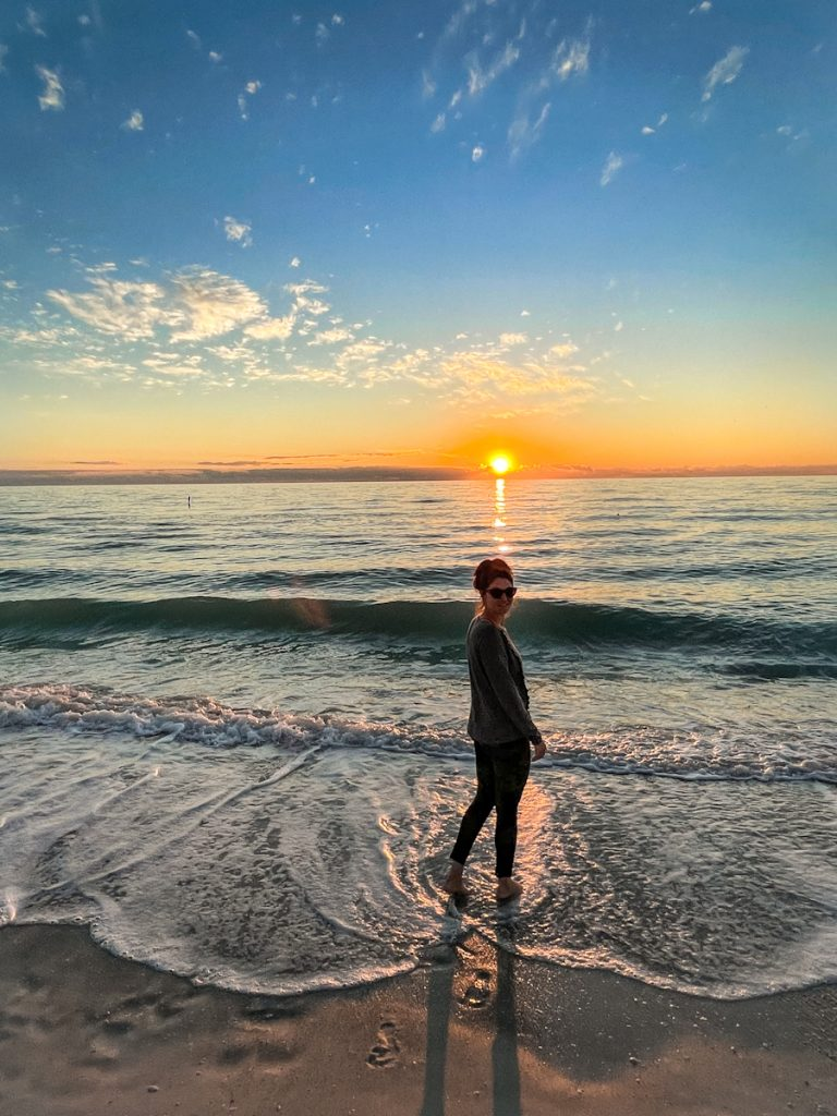 girl walking along the shore of the gulf of mexico at sunset