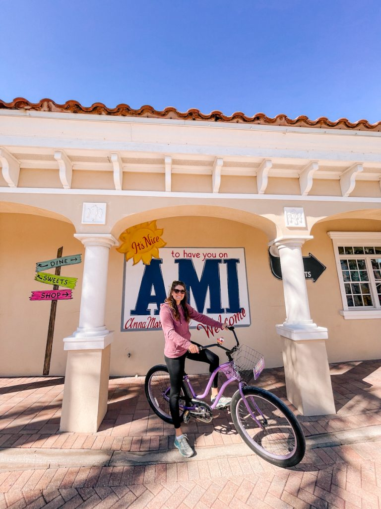 """girl on purple bike posting in front of """"welcome to AMI"""" sign"""