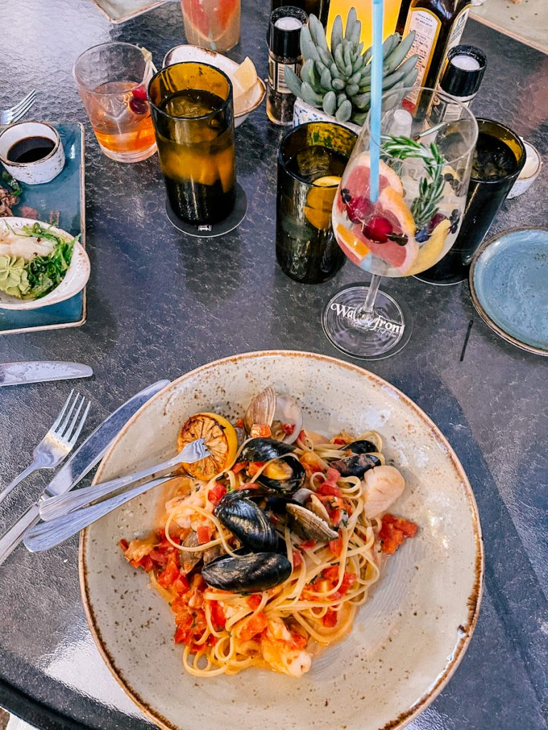 Plate of seafood pasta and gin and tonic